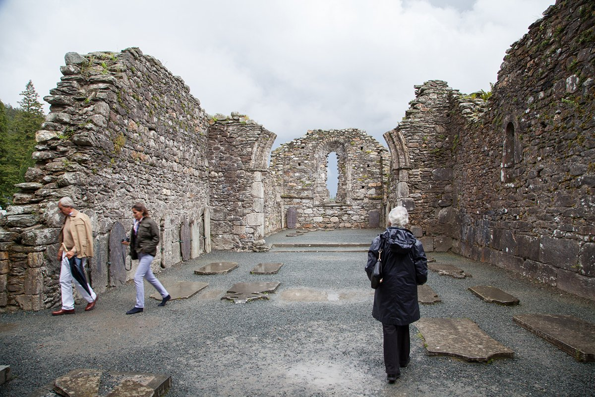 Visitors explore old church ruins at Glendalough
